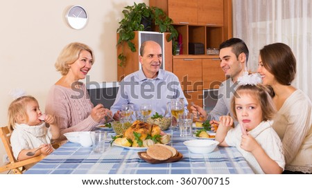 Multigenerational family sitting at the table set for dinner at home