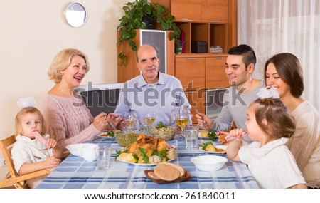 Multigenerational positive family sitting at the table set for dinner