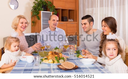Multigenerational smiling family sitting at the table set for dinner