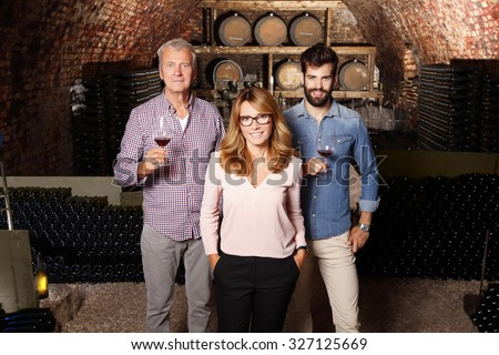 Multigenerational winery owner family standing at wine cellar. Senior winemaker and young sommelier holding a glass of red wine while businesswoman looking at camera and smiling. Small business.  - stock photo
