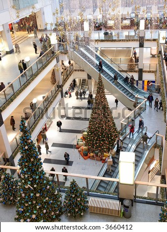 Multilevel shopping mall interior decorated with christmas trees - aerial view - stock photo