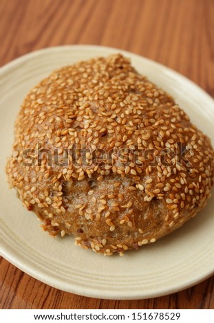multimalt roll or bread roll in plate on wooden table