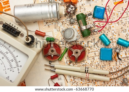multimeter and electronic components on circuit - stock photo