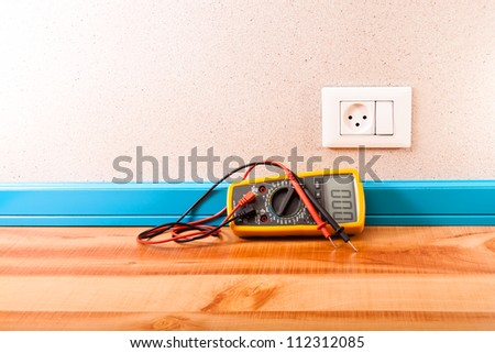 Multimeter and outlet with a switch in the room - stock photo