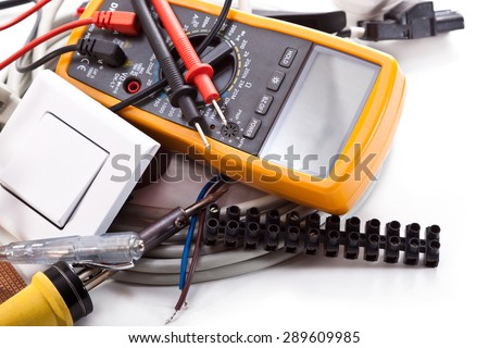 Multimeter, electrical wires, a soldering iron, switch, tester on a white background - stock photo