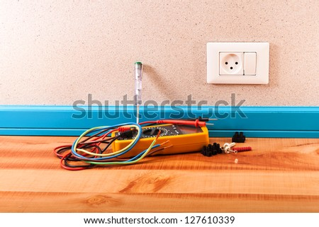 Multimeter, electrical wires, connections for wires on the wooden floor in the room - stock photo