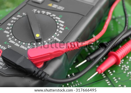 Multimeter on electronic board - stock photo