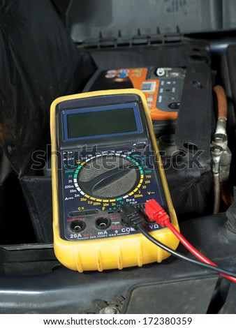 Multimeter set up and ready for taking car battery voltage measurement - stock photo