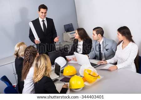 Multinational company of positive russian architects brainstorming in office - stock photo