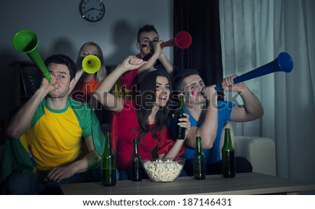 Multinational friends cheering football match at home   - stock photo