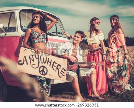Multinational hippie hitchhikers with guitar and luggage on a road - stock photo