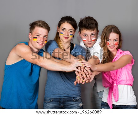 Multinational teamwork. Group of for people with different national flags painted on the faces