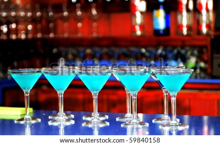 Multiple blue martinis lined up across the bar - stock photo