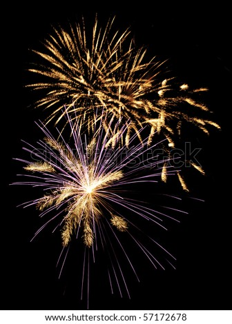 Multiple bursts of fireworks, one blue and white, others golden with motion blur - stock photo