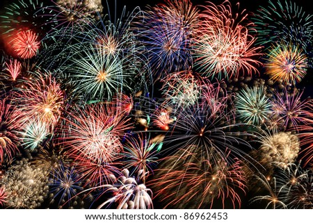 Multiple bursts of multicolored fireworks fill the horizontal frame against a black background - stock photo
