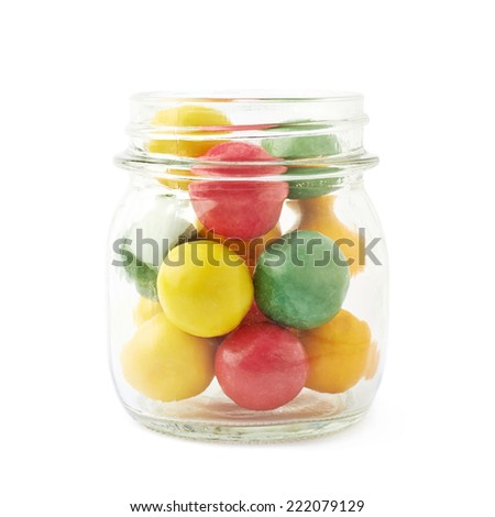 Multiple chewing gum balls in a glass jar isolated over the white background