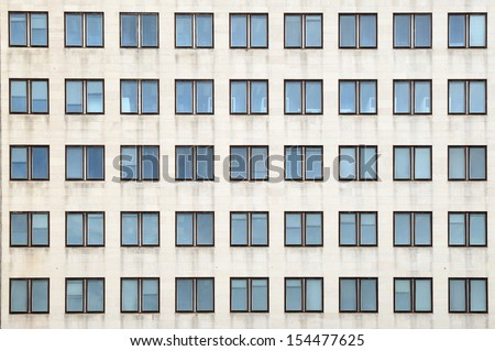 Multiple closed windows on a large office building - stock photo
