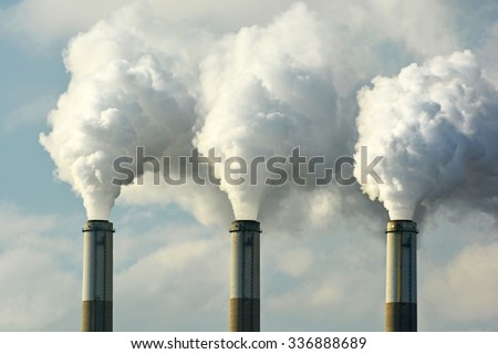 Multiple Coal Fossil Fuel Power Plant Smokestacks Emit Carbon Dioxide Pollution - stock photo