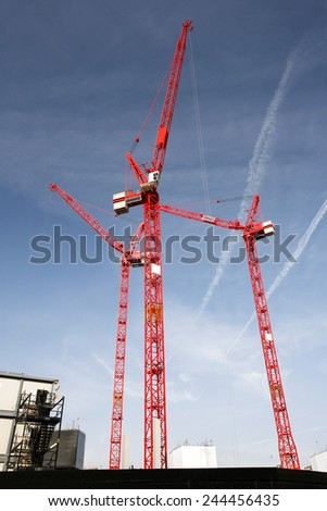 multiple cranes working on huge construction site - stock photo