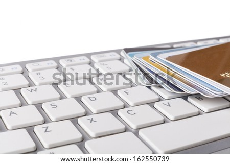 Multiple credit cards on computer keyboard on white background - stock photo