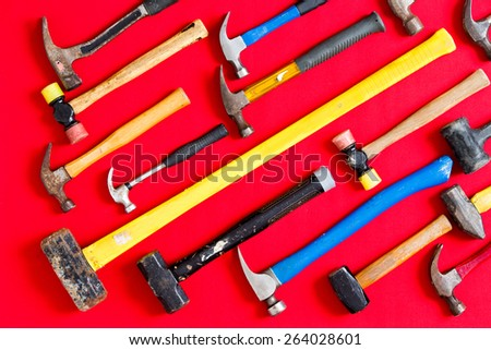 Multiple different mallets and hammers arranged in diagonal lines on a vivid red background in a diversity, DIY, construction, maintenance, and renovation concept, overhead view - stock photo