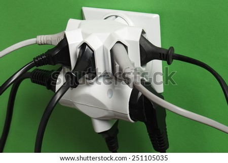 Multiple electric plugs in wall outlet - stock photo