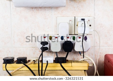 Multiple electricity plugs on adapter risk overloading and dangerous. - stock photo