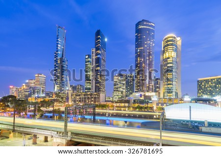 Multiple exposure image of skyscrapers and light trail of trains in downtown Melbourne, Australia at twilight - stock photo