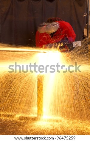 Multiple exposure of welder in workshop manufacturing metal construction by showering sparks from torch. - stock photo