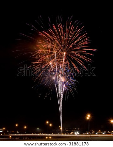 Multiple fireworks bursts against a black sky rise from behind an elevated city expressway. - stock photo
