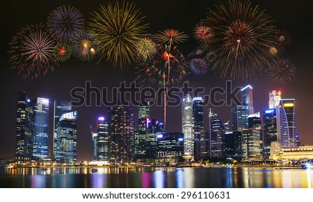 Multiple fireworks exploding high in the sky over modern building in city. - stock photo