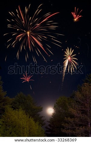 Multiple fireworks explosions above the full moon and trees. - stock photo