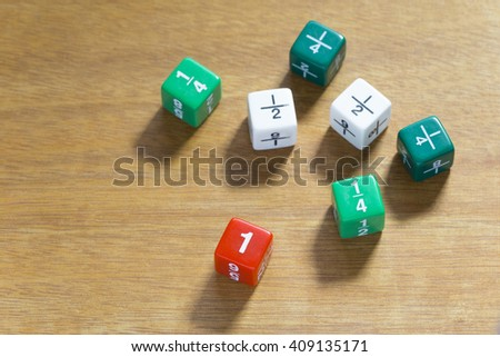 Multiple fraction dices, shown in quarters, halves, and full number set on wood table, selective focus on number one - stock photo