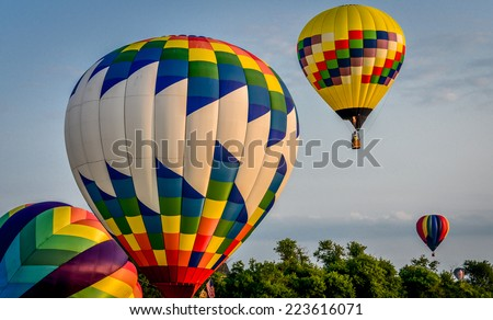 Multiple Hot Air Balloons over Trees - stock photo