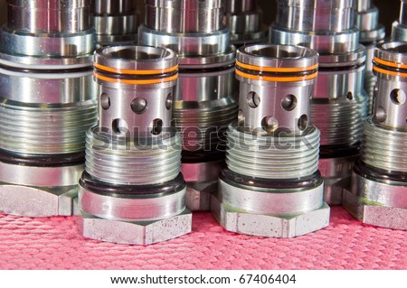 Multiple Hydraulic Cartridge Valves covered in oil on a red shop cloth - stock photo