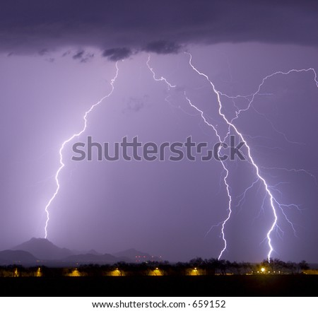 Multiple Lightning bolts and rain with airport hangers in the foreground - stock photo