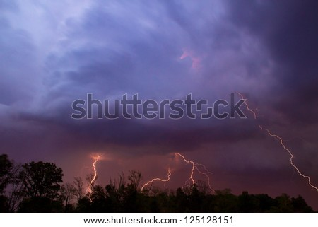 Multiple lightning bolts strike from colorful thunderstorm clouds.
