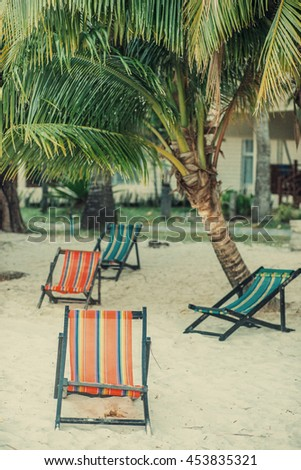 Multiple lounge on the sandy beach chairs in the tree shadow under the palm. Sunset. Vacation postcard concept. Travel inspiration. Vintage effect.