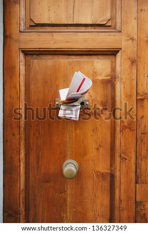 Multiple magazines in a letterbox of a wooden door. Focus is on the newspaper and magazines. - stock photo