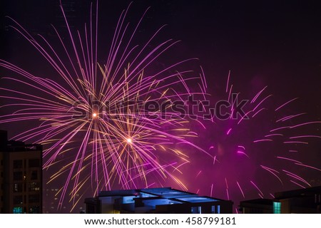 Multiple magenta pink fireworks burst above buildings - stock photo