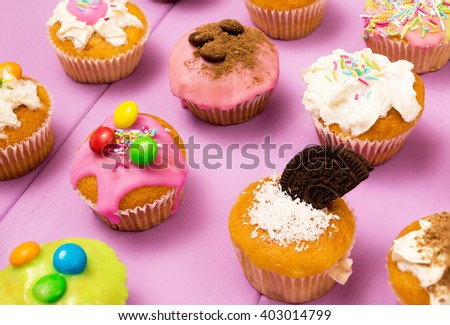 Multiple muffins decorated with multicolored frosting, cocoa powder and beans, candies and whipped cream top view toned selective focus close up - stock photo