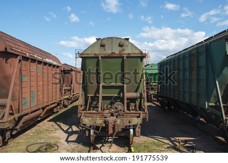 Multiple old industrial train wagons on rail tracks - stock photo
