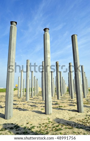 Multiple pilings sunk in river bed will support new bridge under construction - stock photo