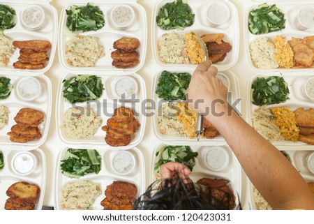 Multiple portions of fresh food being dished out onto individual serving trays - stock photo