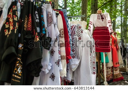 Multiple profile of romanian traditional costumes on mannequins and hangers shown outdoors.