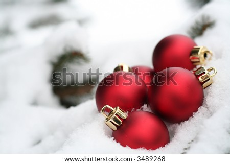 Multiple red Christmas ornaments outside in the snow - stock photo