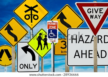 Multiple road signs against a blue cloudy sky. Signs include: giveway, hazard, pedestrian crossing, left turn only, railway crossing and more. - stock photo