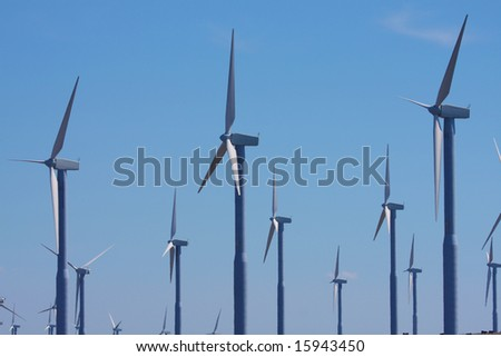 Multiple rows of wind turbines against a summer sky