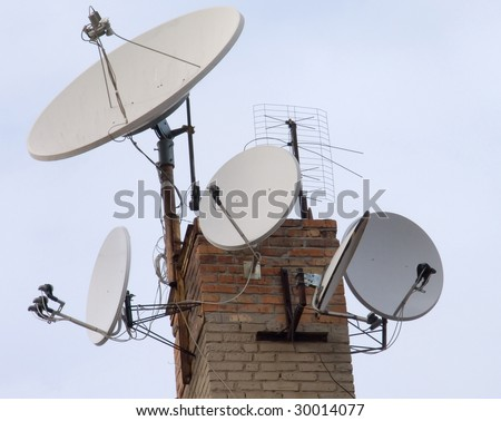 Multiple satellite dishes installed on the roof - stock photo