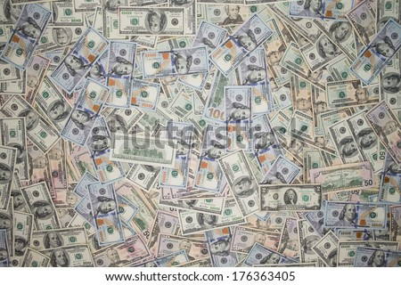 Multiple scattered American 100 dollar banknotes in full frame coverage with corner vignetting viewed from above in a conceptual financial background - stock photo